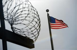 A US flag flies above a razor wire at Gitmo.
