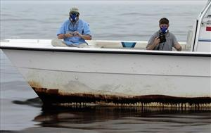 Researchers wear breathing masks as they pass through oil in the Gulf of Mexico.