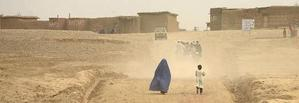 TAJABAD, AFGHANISTAN -- A woman in her burqa walks along the dusty dirt road to the entrance of the Shamshatto refugee camp in Tajabad, Pakistan, Wednesday, October 31, 2001.