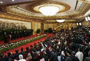 Chinese President Hu Jintao, left, delivers his speech and introduces the new members of the Politburo Standing Committee from left are Public Security Minister Zhou Yongkang, Liaoning Party Secretary Li Keqiang, head of Communist Party Ideology Department Li Changchun, Premier Wen Jiabao, National People's Congress Chairman Wu Bangguo, Chairman of...