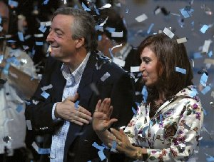 Argentina's president and his wife presidential candidate Cristina Fernandez de Kirchner wave  to supporters at their party's headquarters in Buenos Aires, Sunday, Oct. 28, 2007. Early official results and several major exit polls suggested that Fernandez de Kirchner won the presidency Sunday by a large enough margin to avoid a...