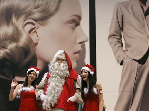 Santa Claus from Finland, with two models walk on street during a Christmas promotional event for a shopping center in downtown, Hong Kong Thursday, Nov. 29, 2007.  (AP Photo/Kin Cheung)