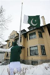 The flag of Pakistan is lowered to half staff in front of Pakistan's Embassy in Ottawa on Thursday, Dec. 27, 2007 following the assassination of former prime minister Benazir Bhutto. (AP Photo/THE CANADIAN PRESS, Sean Kilpatrick)