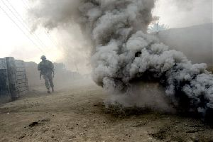 A U.S. army soldier from Ghostrider Company, 3rd Squadron, 2nd Stryker Cavalry Regiment runs through smoke generated by a smoke grenade during Operation Phantom Phoenix in the volatile Diyala province, about 90 kilometers north of Baghdad, Iraq. (AP Photo/Marko Drobnjakovic)