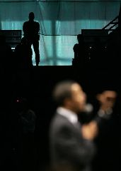 A security guard watches Democratic presidential hopeful Sen. Barack Obama, D-Ill., address a crowd of over 9,000 during a rally in Birmingham, Ala., Sunday, Jan. 27, 2008. (AP Photo/Charles Rex Arbogast)