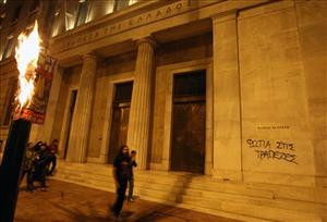 A poster burns in front of Bank of Greece headquarters as the graffiti reads ''Burn banks'' during a march in central Athens last month.
