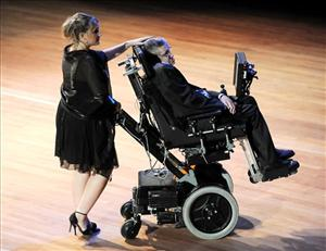 An aide helps guide British physicist Stephen Hawking off the stage at the 2010 World Science Festival opening night gala performance at Alice Tully Hall on Wednesday, June 2, 2010 in New York.