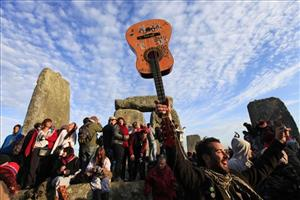 People dance as they celebrate the summer solstice shortly after 04:52 am at the Stonehenge monument, England, early Monday, June 21, 2010.