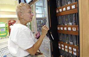 In this June 25, 2010 photo, Jacqueline Love purchases her first bottle of wine from the Pennsylvania Liquor Control Board's self-serve wine kiosk at a Giant food store, in Harrisburg, Pa.