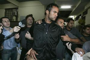 Flamengo soccer team's goalkeeper Bruno Fernandes de Souza is surrounded by journalists and police officers as he is moved to a homicide police station in Rio de Janeiro.