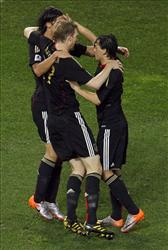 Germany's Sami Khedira, top left, celebrates after scoring with his teammates Per Mertesacker, center, and Mesut Oezil during the World Cup third-place soccer match between Germany and Uruguay.