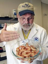 A seafood tester demonstrates how to smell for oil contamination as he moves the air across a bowl of shrimp at NOAA's seafood inspection program in Pascagoula, Miss.