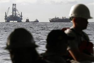 Vessels assisting in the capping of the Deepwater Horizon oil wellhead leak are seen past crew members on the Pacific Responder oil skimming vessel on the Gulf of Mexico near the coast of Louisiana Friday, July 16, 2010.