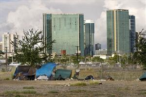 With the Honolulu skyline in the background, a homeless camp is seen in an empty lot near Kaakako Park, Monday, July 12, 2010 in Honolulu.  Homelessness increased 15% on Oahu since last year.