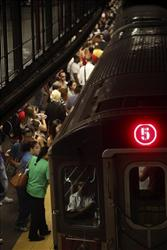 Commuters board a subway train in New York, Wednesday, July 28, 2010.