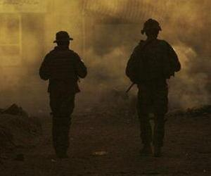 U.S. Army soldiers are seen through the haze of burning trash as they patrol in Baqouba, Iraq, Oct. 6, 2008.