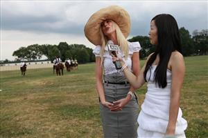 In this June 12, 2010 file photo, Michaele Salahi, left, is interviewed by Ariuka Ulziibayar at the America's Polo Cup Championships, which the Salahis hosted, by the National Mall in Washington.
