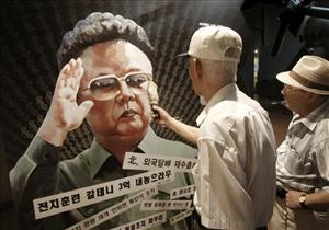 A visitor points with am umbrella at a poster of North Korean leader Kim Jong Il, painted by North Korean defector Sun Moo, at the Korea War Museum in Seoul, South Korea, Tuesday, Aug. 31, 2010.