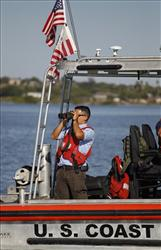 A man on a U.S. Coast Guard vessel uses binoculars on Falcon Lake in this file photo.