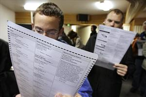 In this file photo, two votes look over the ballots.