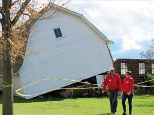 Two Red Cross workers walk away from a barn that was lifted off its foundation by a tornado Tuesday, Oct. 26, 2010, in Mount Pleasant, Wis.