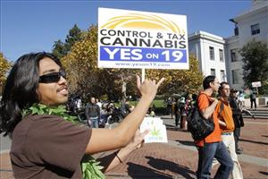 California Proposition 19 supporter Kainoa Ignacio holds up a sign as he makes a Hawaiian greetings sign during a rally at the University of California, Berkeley campus, Nov. 1, 2010.