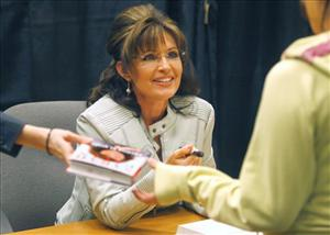 Sarah Palin greets fans and supporters as she signs her book America by Heart, during a book signing event at a Barnes & Noble store on Tuesday, Nov. 23, 2010, in Phoenix.