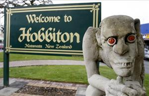 A sculpture of Gollum stands in front of a welcome sign, in Hobbiton Town, Matamata, New Zealand.