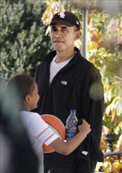 President Barack Obama waits as his daughter Sasha walks by after a basketball outing with both of his girls and some of their friends, Sunday, Nov. 28, 2010, in Washington.