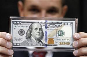 In this Aug. 10, 2010 photo, United States Treasury Department Bureau of Engraving and Printing manager Kevin Brown displays a new $100 bill at the World's Fair of Money in Boston.