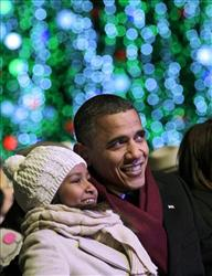 President Obama smiles as he and his youngest daughter, Sasha, 9, attend the National Christmas Tree lighting ceremony on the Ellipse, just south of the White House,Dec. 9, 2010.