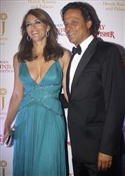 In this photo taken Friday, June 18, 2010, British actress-model Elizabeth Hurley, left, and her husband businessman Arun Nayar look on during an event in Mumbai, India.