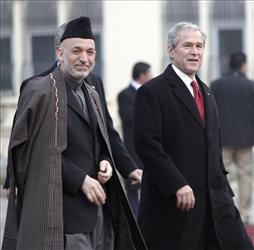 In this Monday, Dec. 15, 2008, file photo, President George W. Bush walks with Afghan President Hamid Karzai at the Presidential Palace in Kabul, Afghanistan.