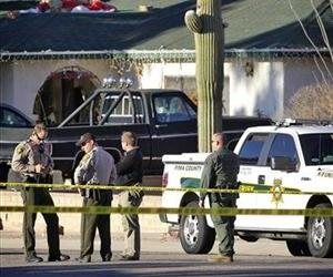 Law enforcement officals stand across the street from the house of Jared L. Loughner Saturday, Jan. 8, 2011 in Tucson, Ariz.