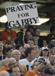 Fans pause during a moment of silence  for Rep. Gabrielle Giffords and other Tuscon shooting victims before the BCS National Championship NCAA college football game in Phoenix yesterday.