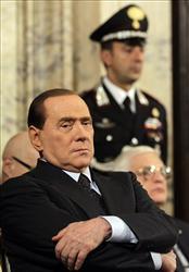 Italian premier Silvio Berlusconi sits as he listen to a speech.