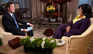 This undated photo made available by CNN, shows Piers Morgan, left, host of Piers Morgan Tonight interviewing Oprah Winfrey.