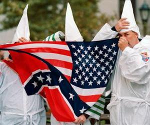 Three members of the Ku Klux Klan hide behind a combination Confederate and American flags during a rally in New York in this file photo.