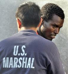 File photo of a US marshal escorting a suspected Somali pirate into court in Virginia.