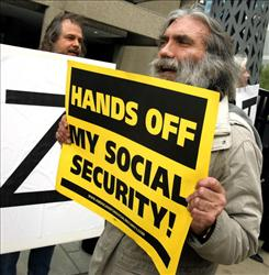 Frank Sawyer (R) displays a sign during a demonstration in front of the Social Security Administration office April 26, 2005 in Chicago, Illinois.