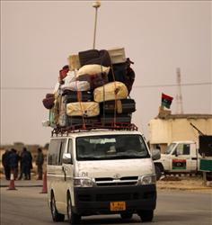 A mini bus laden with suitcases drives out of Benghazi past a rebel checkpoint.