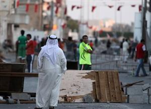 Residents of the Shiite Muslim village of Malkiya, Bahrain, look over the makeshift barricades they said they replaced yesterday after they were cleared when riot police and tanks moved through town.