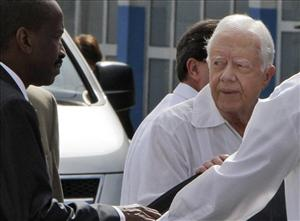 Former President Jimmy Carter, right, looks at a security agent as he arrives to the Jose Marti airport in Havana, Cuba, Monday, March 29, 2011.