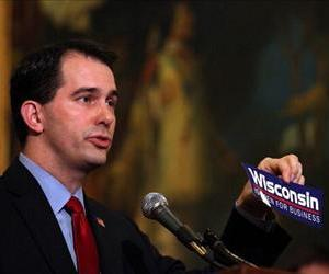 Scott Walker holds up a 'Wisconsin is open for business' bumper sticker as he speaks during a ceremonial bill signing outside his office at the Wisconsin State Capitol on March 11, 2011.