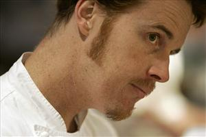 In this April 3, 2008 file photo, chef Grant Achatz looks across the Alinea restaurant kitchen at his small army of chefs at they work in the kitchen at Alinea in Chicago.