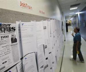In this April 1, 2011, photo, an unemployed man looks at job listings in Menlo Park, Calif.