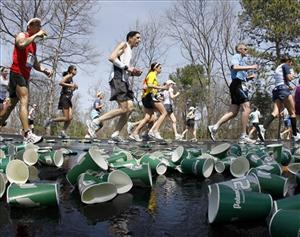 Runners make their way through discarded cups from a water station during the running of the 115th Boston Marathon through Wellesley, Mass., Monday, April 18, 2011.
