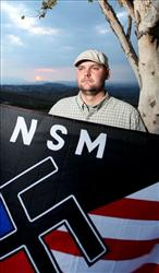 In  this file photo from last year, Jeff Hall holds a neo-Nazi flag near his home in Riverside, Calif.