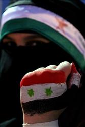 A Syrian protester holds up her hand, painted with the colors of the national flag at a demonstration demanding that Syria's President Bashar Assad step down in Amman, Jordan, Saturday, May 7, 2011.