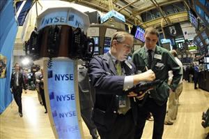 FILE - In this file photo taken May 6, 2011, Warren Meyers, left, talks to James Macona of NYSE Euronext on the floor of the New York Stock Exchange.